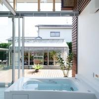 建具を開けるとテラスと一体になる開放的な浴室。 向かいは端正に育てられている蘭の温室